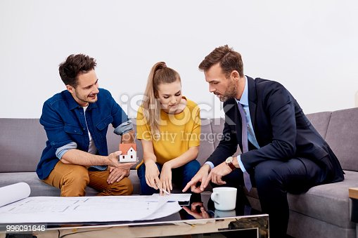 istock Young couple discussing construcion plans with middle-aged real estate agent 996091646