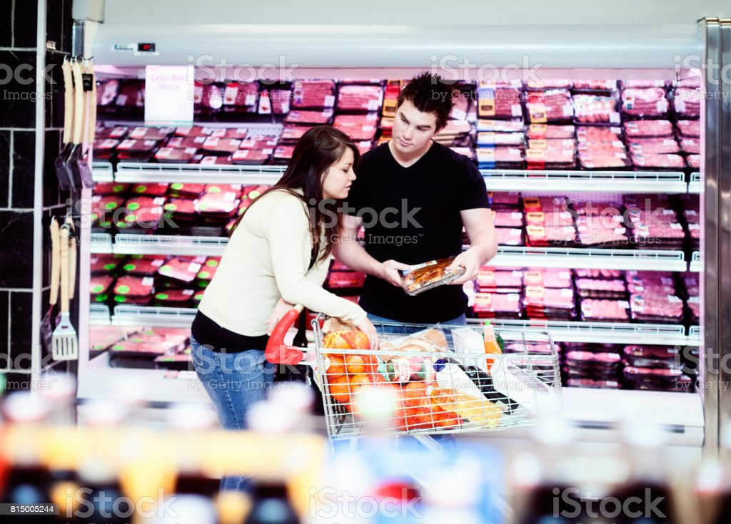 Young couple discussing meat purchase in supermarket butchery stock photo