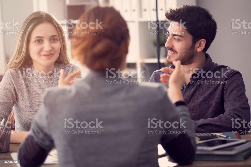 Jeune couple discutant avec un agent féminin - Photo