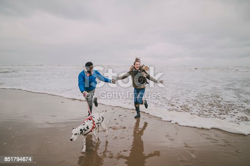 istock Young Couple Dodge Waves On Winter Beach 851794674
