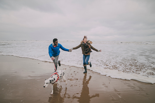 Young Couple Dodge Waves On Winter Beach
