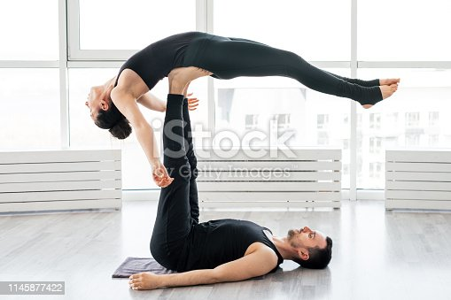 istock Young couple doing acro yoga in pair at studio 1145877422