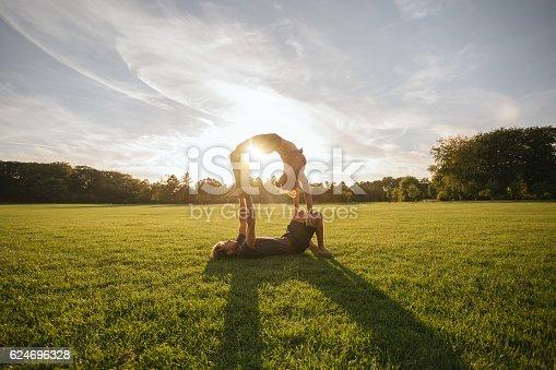 istock Young couple doing acrobatic yoga on lawn 624696328