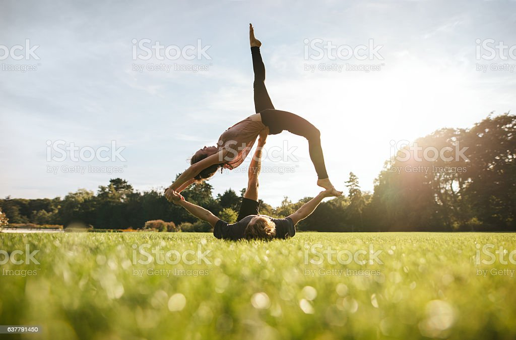 Young couple doing acrobatic yoga on lawn stock photo