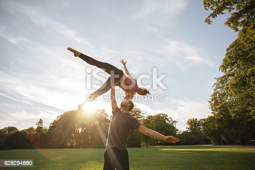 istock Young couple doing acroyoga at the park 628294880