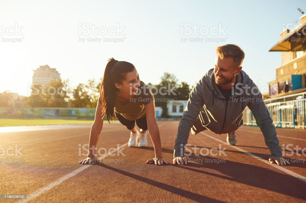 Junges Paar beim Pushup im Stadion - Lizenzfrei Aktiver Lebensstil Stock-Foto