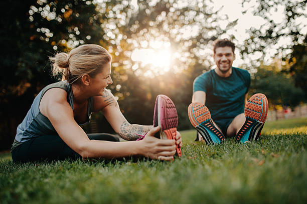 young couple doing their stretches in the park - jacob ammentorp lund stock pictures, royalty-free photos & images