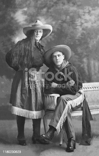 Vintage 1915´s portrait of a handsome young couple dressed up as cowgirl and cowboy adn getting ready for a masquerade ball party in Amsterdam, the Netherlands.