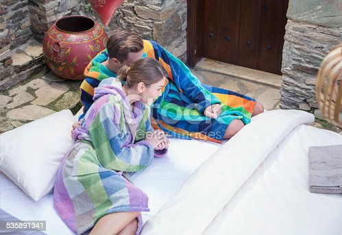 536952169 istock photo Young couple dressed in bathrobe at garden 535891341