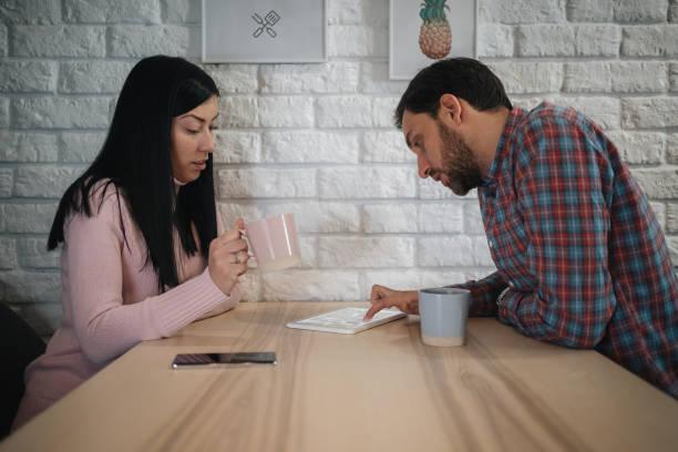 pareja joven bebiendo café y leyendo noticias en una tableta en su comedor - happy couple sharing a cup of coffee fotografías e imágenes de stock