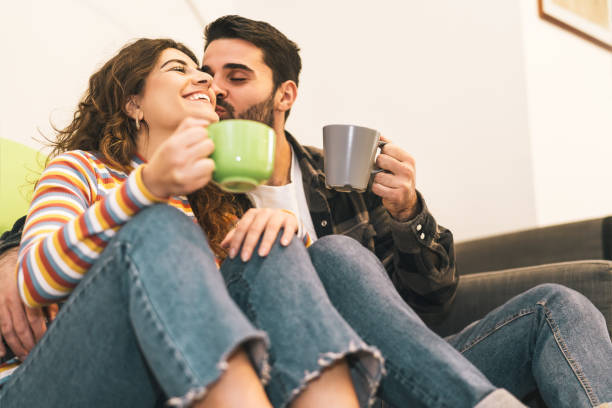pareja joven bebiendo taza de café sentado en el piso junto sofá - felices amantes teniendo momentos tiernos juntos en casa - relación de amor y la gente joven concepto de estilo de vida - happy couple sharing a cup of coffee fotografías e imágenes de stock