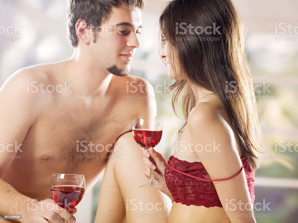 Young couple drinking red wine on the bed in bedroom stock photo