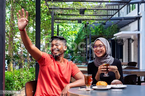 happy multi ethnic couple waving hand and smiling while having afternoon tea is a sidewalk