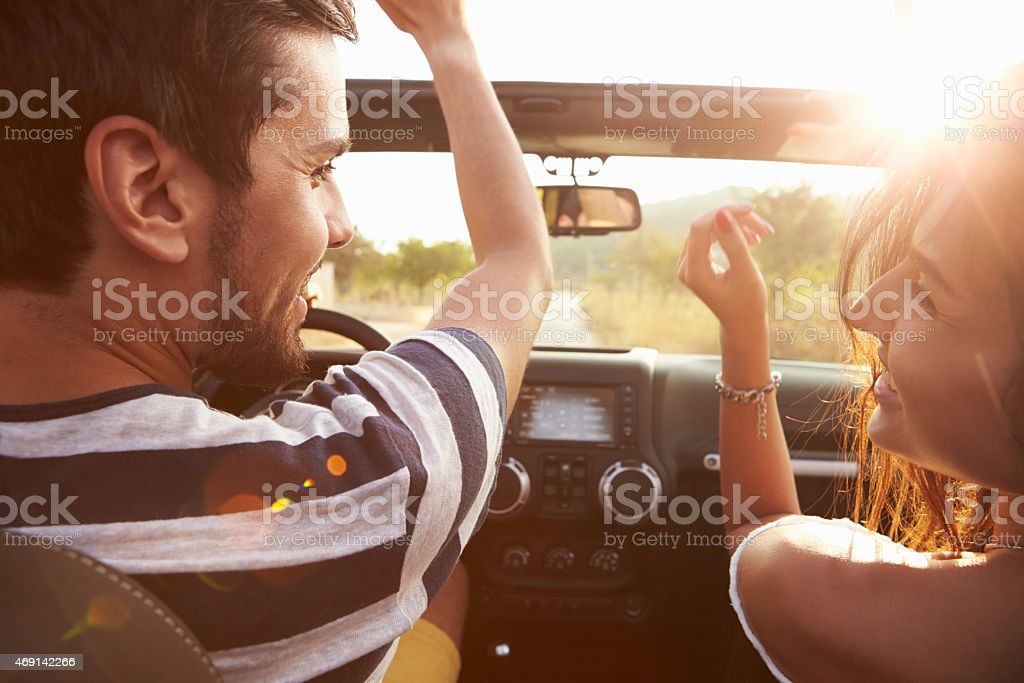 Young Couple Driving Along Country Road In Open Top Car stock photo