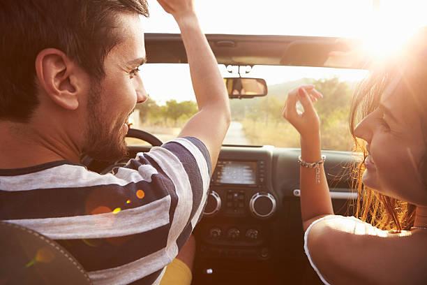 casal jovem dirigindo pela estrada rural em aberto carro top - viagem de primeira classe - fotografias e filmes do acervo