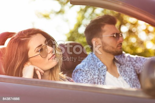 1030408008istockphoto Young Couple Driving Along Country Road In Open Top Car 843874666