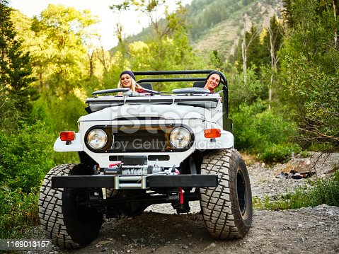 A young couple driving an off road 4x4 vehicle in a wilderness area.