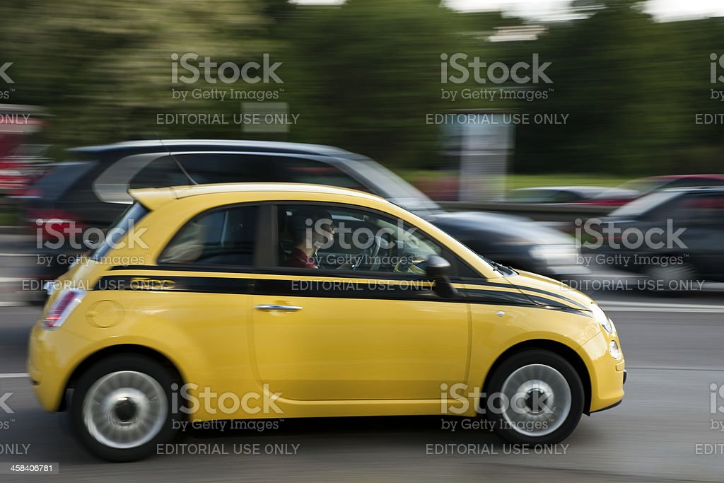 Young Couple Driving Fiat 500 on the Busy Street royalty-free stock photo