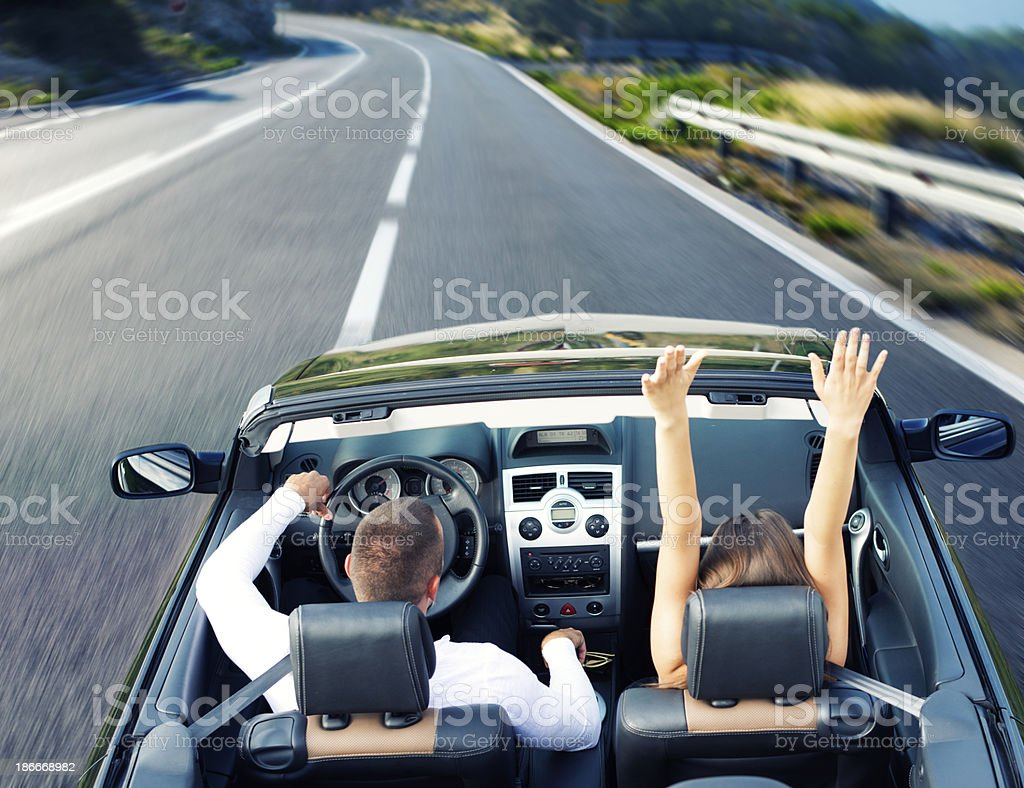 Young couple driving in a cabriolet car with the top down stock photo