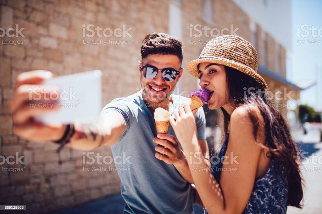 Jovem casal comendo sorvete e assumir selfies férias de verão - foto de acervo