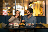 Young couple in a Chinese restaurant eating noodles and sushi. Both about 25 years old, Caucasian.