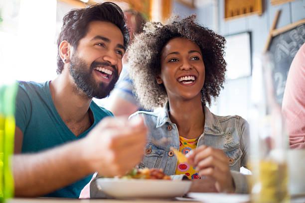 junges paar essen in einer bar - tagesgericht stock-fotos und bilder