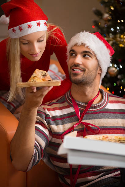young couple eating pizza beside christmas tree - schnelles weihnachtsessen stock-fotos und bilder