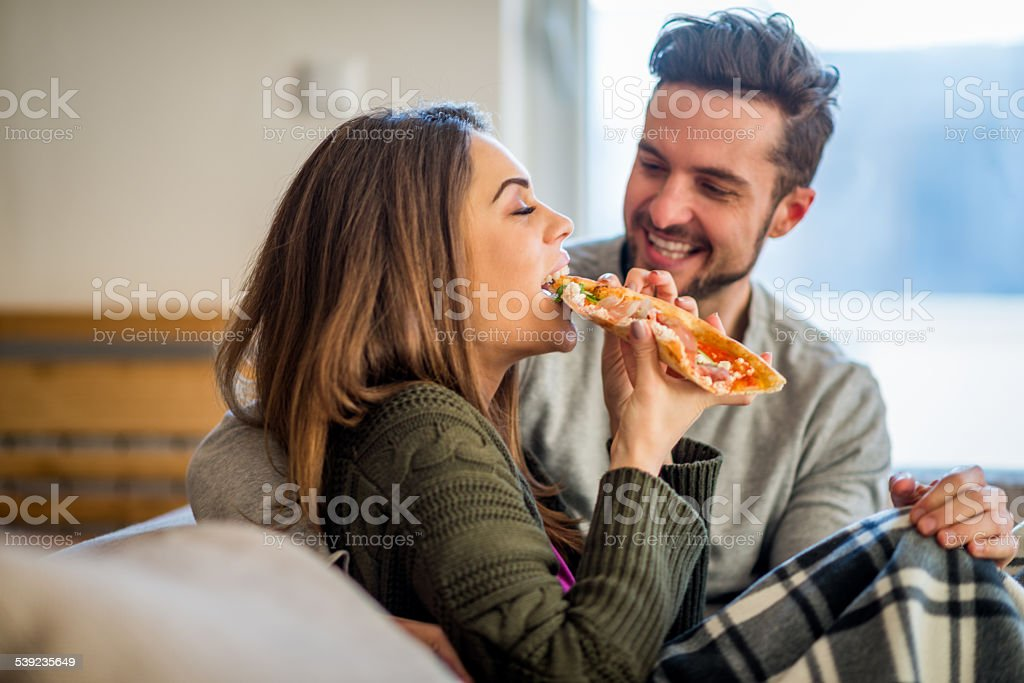 Young couple eating pizza in bed royalty-free stock photo