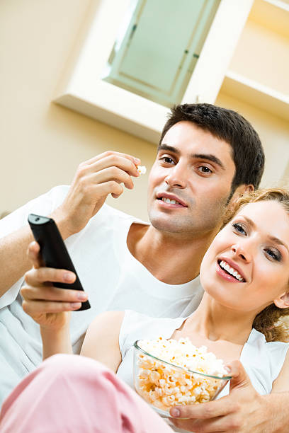 Young couple eating popcorn and watching TV together at home stock photo