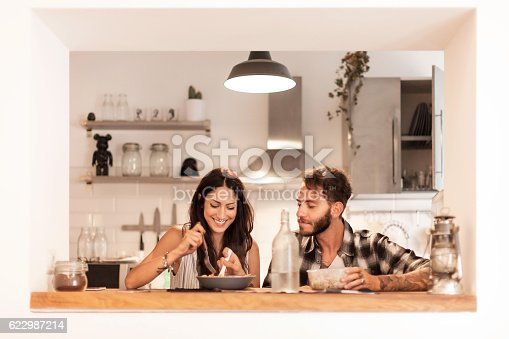 istock Young couple eating together at home 622987214