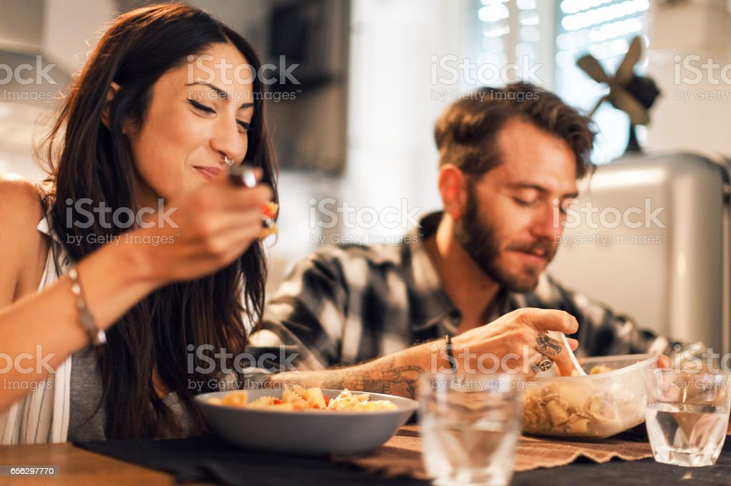 Young couple eating together at home stock photo