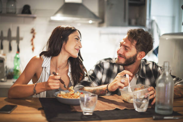 young couple eating together at home - family dinner stock photos and pictures