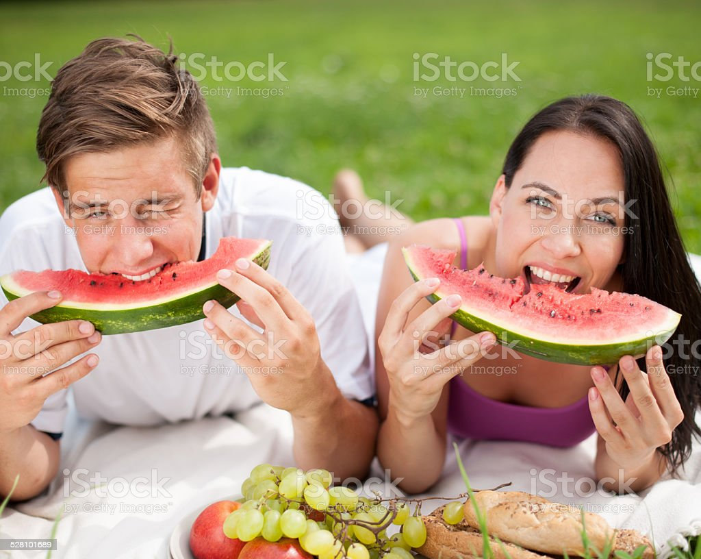 Young couple eating water melon for picnic royalty-free stock photo