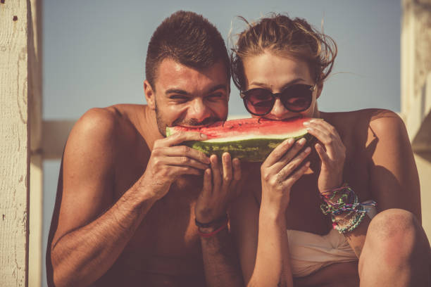 Young couple eating watermelon together stock photo