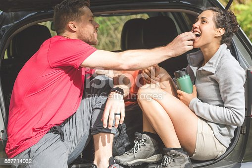 Young couple eats a snack in the back of their car after a brisk morning hike. He is holding something in his hand and putting it in her mouth. She is laughing. They're both wearing hiking boots.
