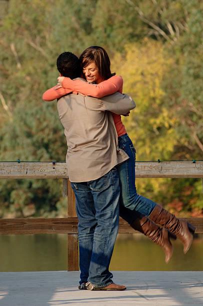 junges paar umarmung am pier in der nähe von lake - mark tantrum stock-fotos und bilder