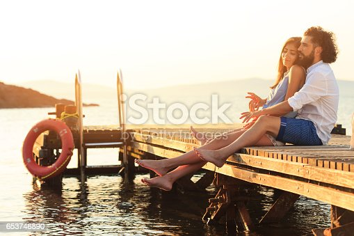 Young people embracing and sitting on a pier. Both with casual clothes, barefoot, man with beard and curly hair, woman with long hair.