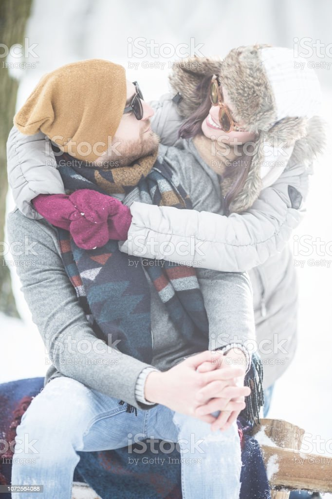 Young couple embracing in winter outdoors stock photo
