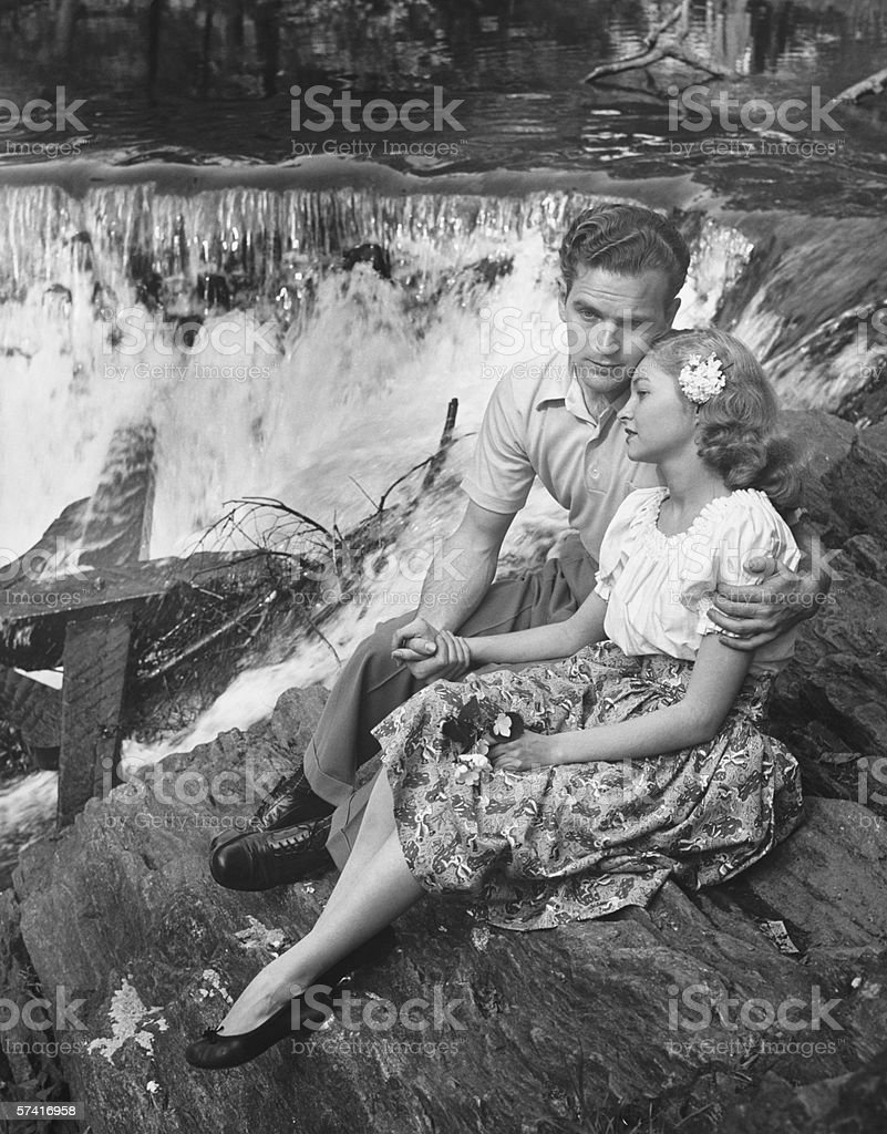 Young couple embracing near waterfall, (B&W) stock photo