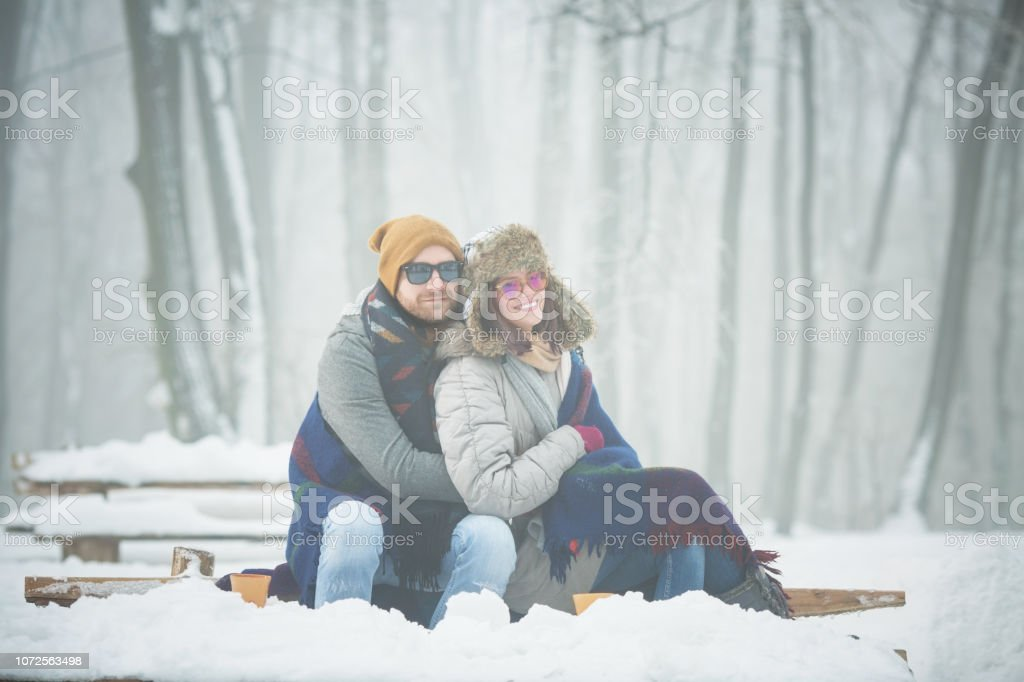 Young couple embracing on bench in winter outdoors stock photo