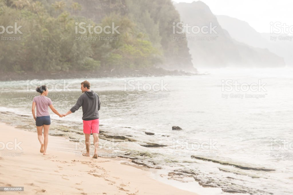 Jeune couple jouir d'une promenade le long sur la belle plage de Hawaii photo libre de droits