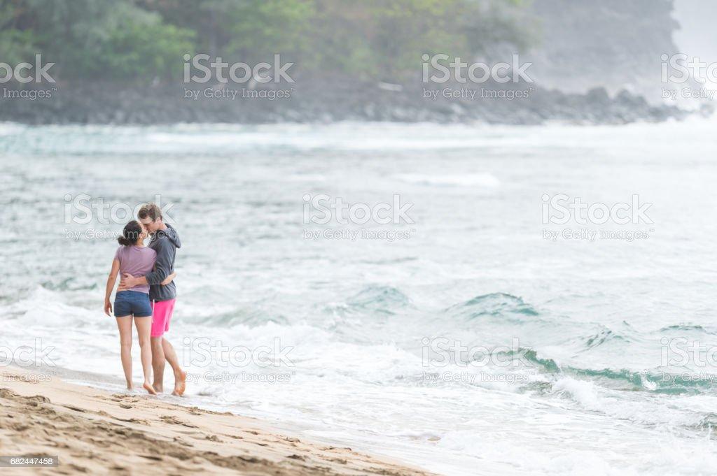 Young couple enjoy a walk along on beautiful sandy Hawaii beach royalty-free stock photo