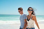 Beautiful woman with man wearing sunglasses walking on beach.. Young couple enjoying honeymoon after marriage at sea. Happy casual couple holding hands and walking at the beach with copy space.