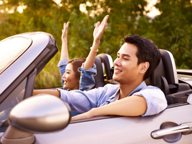 young couple enjoying a car ride - asian travel in car stock photos and pictures