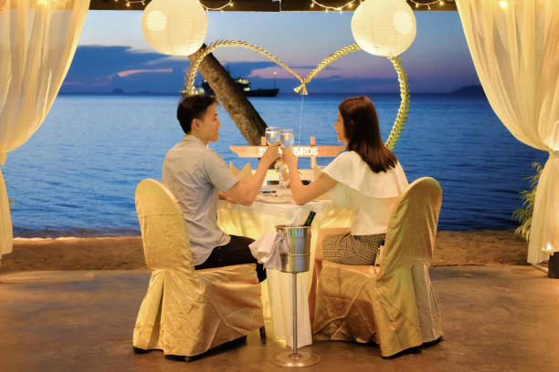 Young couple enjoying a romantic dinner by candlelight, outdoor stock photo