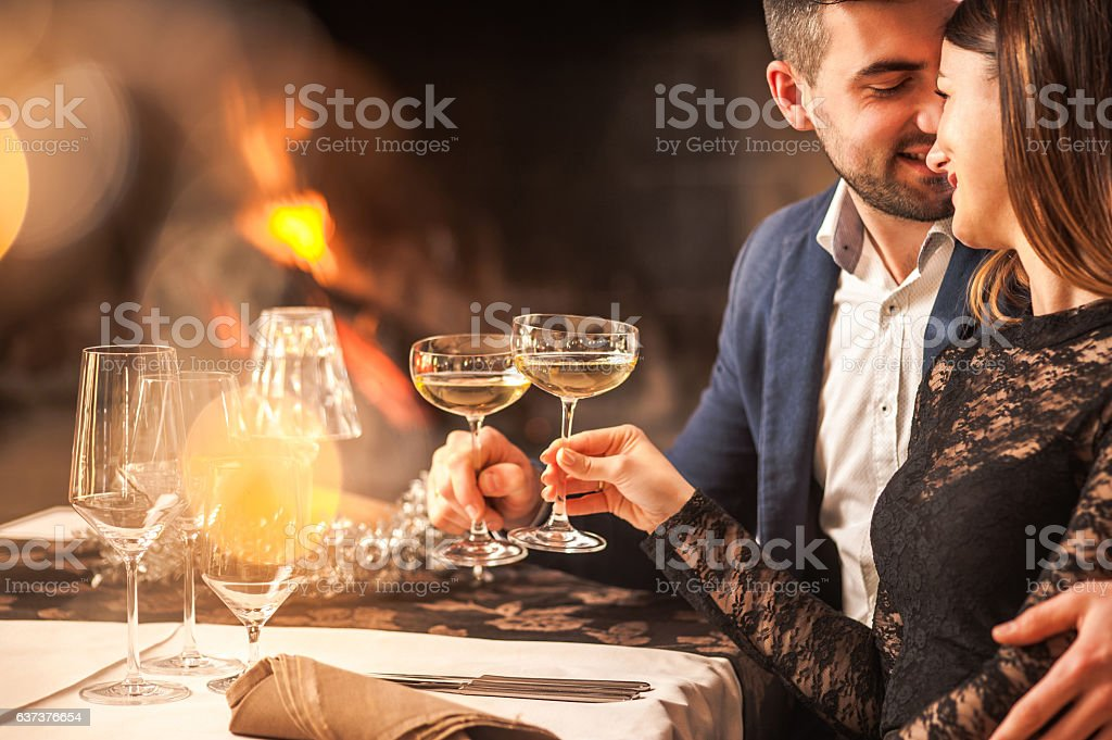 Young Couple Enjoying a Romantic Dinner next to a Fireplace stock photo