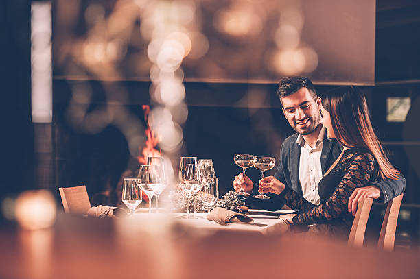 young couple enjoying a romantic dinner together - date night stock pictures, royalty-free photos & images