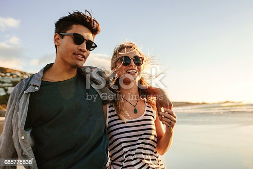 Portrait of handsome young man with his beautiful girlfriend on beach. Young couple enjoying a summer day on seashore.