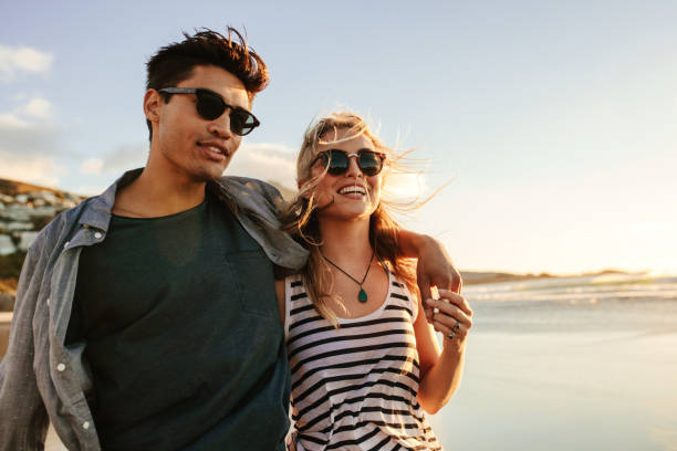 young couple enjoying a summer day on seashore - moda urbana - fotografias e filmes do acervo