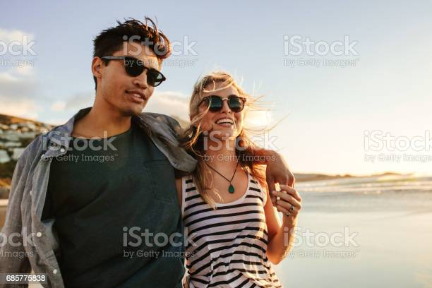 Photo of Young couple enjoying a summer day on seashore